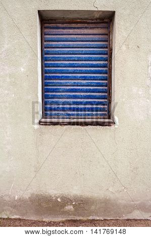 Window in a white plaster wall protected with old rusty metal blinds