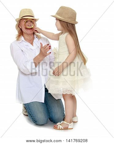 Cute little girl with long blond hair in white dress and hat . The girl looks at through a magnifying glass, the nose of his grandmother - Isolated on white background
