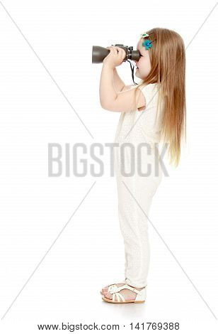Cute little girl with long blond hair below the shoulders , in a white jumpsuit , keep the angle big binoculars . the little girl turned sideways to the camera and looks away