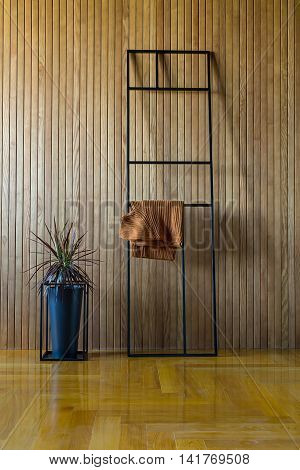 Black metal frame stand which leans on the wooden wall. Brown pullover hangs on the stand. Near the stand there is a plant in a black pot on the black metal stand. On the floor there is a parquet.