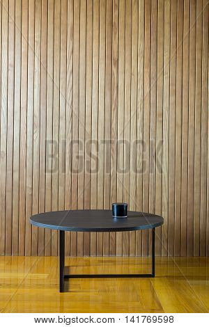 Black wooden round table with metal legs on the background of the wooden wall. There is a dark glass box on the table. On the floor there is a parquet. Indoors. Horizontal.