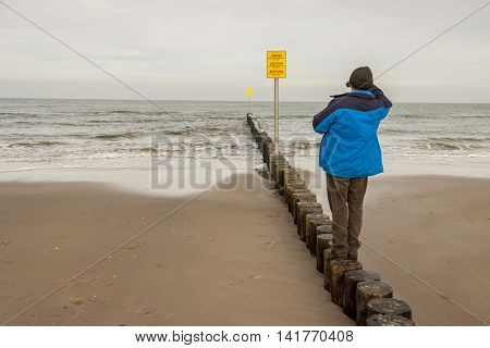 Man on wooden breakwater in Kolobrzeg Poland.