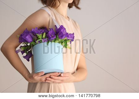 Woman holding box with purple bellflowers on light background