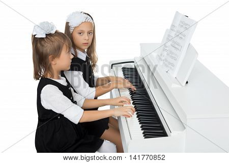 2 cute little girls play in four hands on the piano - Isolated on white background