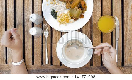 The lady sitting at the wooden table is devouring a plate with meals. The lady is using cutlery utensils to cut her dish meal in small bites. Top view. Unusual POV.