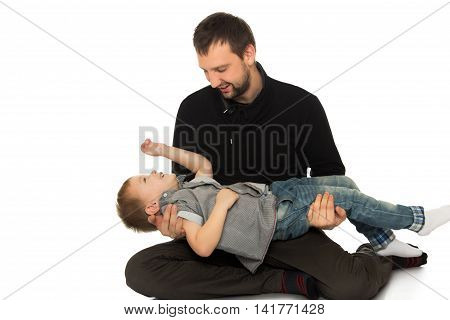 Father and son frolic on the floor. Dad keeps son in his hands - Isolated on white background