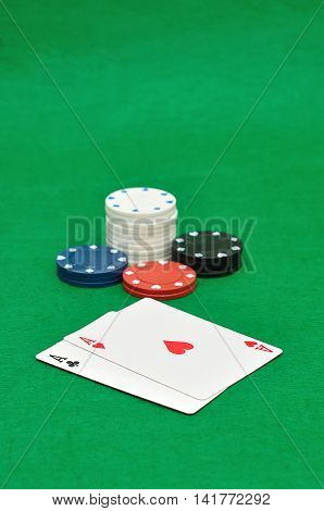 Different poker chips with two aces on a green background