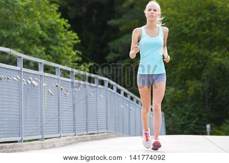 Beautiful young slim blonde woman running or jogging on a bridge. Stamina workout a summer evening.