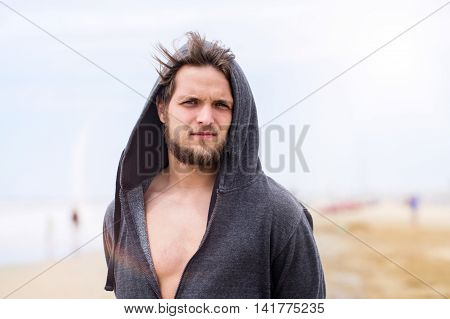 Hipster man on beach, wearing gray hooded sweatshirt, sunny summer. Enjoying time at seaside.