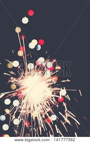 The holiday sparkler with colored balls background
