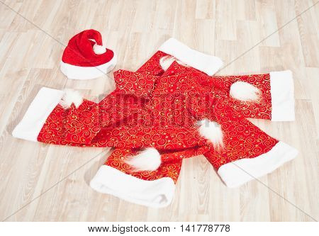 Christmas red hat with white tassel on a wooden floor
