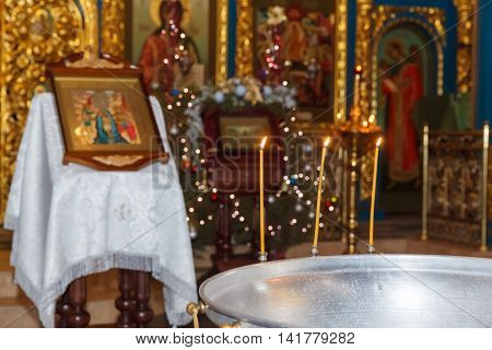 Orthodox baptism bowl of holy water and candles. Russia