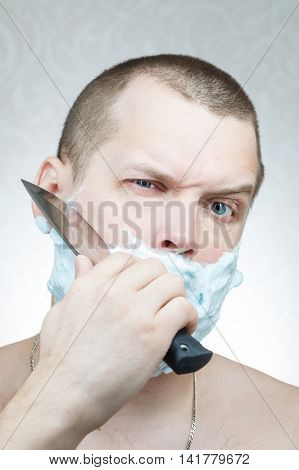young white man shaves his beard a large knife
