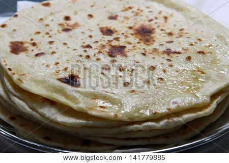 A close up of a stack of buttered Kulcha