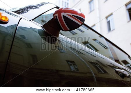 vintage car detail, concept of British Patriotism shown as flag on mirror, trees in reflection windshield, body part close up