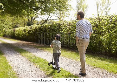 Rear View Of Father And Son Walking In Summer Countryside