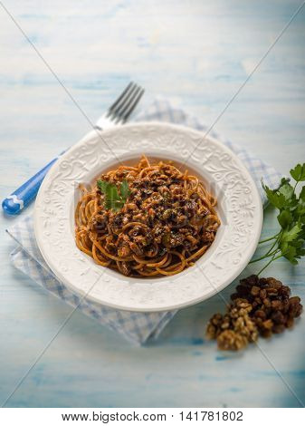 spaghetti with tomato nuts and dried grape, selective focus