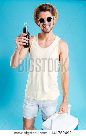 Smiling young man in hat and sunglasses holding cooling bag and bottle of soda over blue background