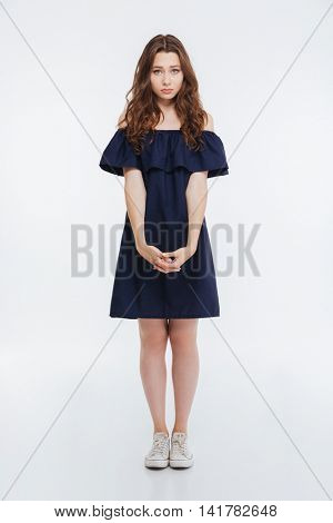 Sad upset young woman in black dress and white sneakers standing over white background