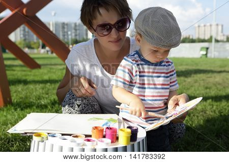 Mother with her son drawing gouache in park