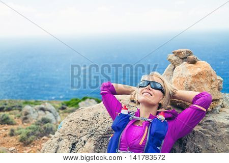 Trail running woman relaxing in mountains after run healthy lifestyle on inspirational beautiful day. Motivation training and working out runner jogging and exercising outdoors in nature Crete Greece.