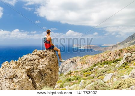 Hiker climber or runner man looking at beautiful ocean and mountains resting and celebrate inspirational landscape view. Fitness sport motivation outdoor in wild summer nature.