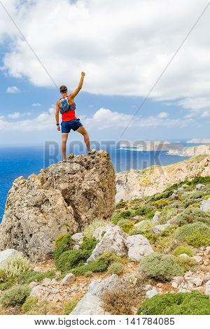 Success climbing and achievement running or hiking accomplishment. Man celebrating with arms up outstretched in mountains climbing rocky trail path outdoors. Motivation and inspiration concept.
