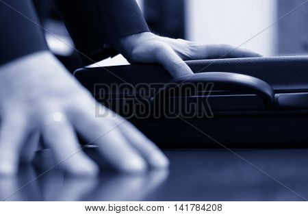 Business meeting detail businessman hand on the briefcase closeup blue toned