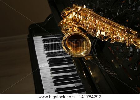 Saxophone lying on the piano, close up