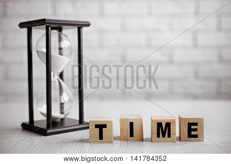 Word TIME with hourglass on white table