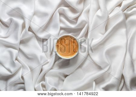 Cup of coffee on a white silk fabric. Espresso with froth in the form of smiley face and scattered beans. Top view.