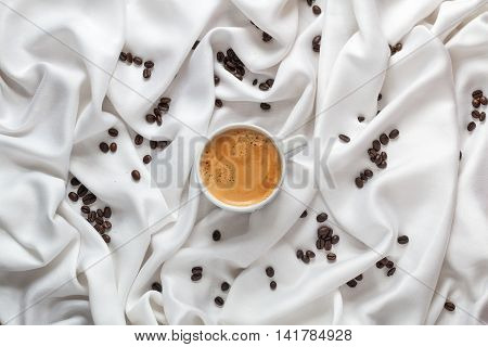 Cup of coffee on a white silk fabric. Espresso with froth in the form of smiley face and scattered beans. Top view