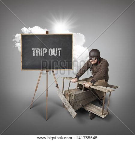 Trip out text on blackboard with businessman and wooden aeroplane