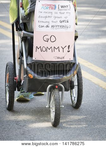 NEW YORK CITY -  JULY 24 2016: A sign of support hangs on a baby stroller in Central Park for female athletes competing in the NYC Triathlon Race on a course that includes swimming, cycling, and running.