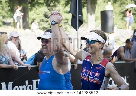 NEW YORK CITY -  JULY 24 2016: Athletes cross the finish line of the NYC Triathlon Race in Central Park. The run is 10 kilometers and the race is the only International Distance triathlon in the city.