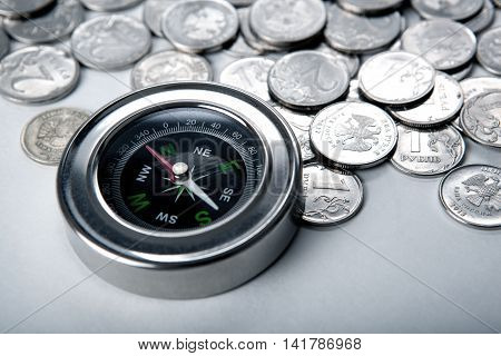 pile of coins with compass close up