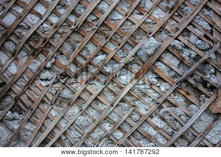 Crumbling plaster and protruding from under her lath
