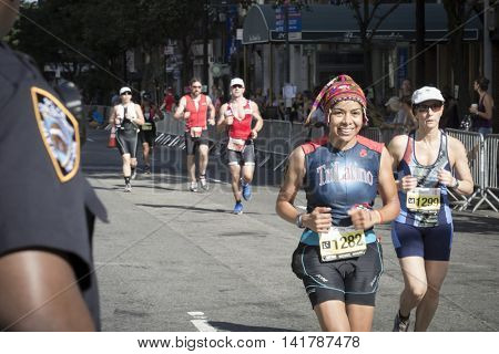 NEW YORK CITY -  JULY 24 2016:  Athletes competing in the NYC Triathlon Race on West 72nd St cross over Central Park West. The run is 10k and the race is the only International Distance triathlon in the city.