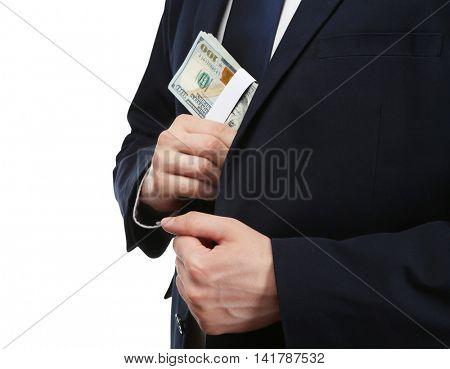 Businessman putting banknotes in suit pocket. Corruption concept
