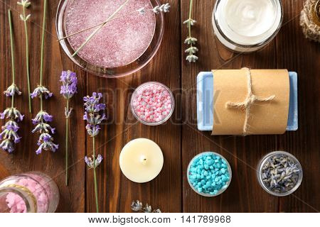 Lavender with soap, sea salt and candle on wooden background. Treatment concept