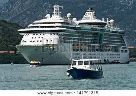 Cruise ship anchored in the Bay of Kotor Montenegro with small boats transferring passengers.