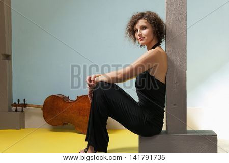 portrait of young woman with her cello, interior