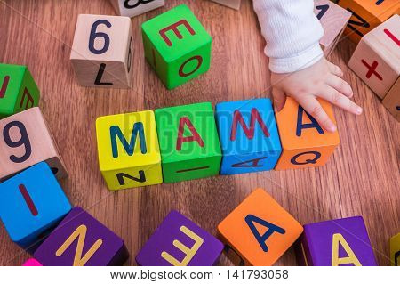 Baby Is Playing With Colorful Cubes And Writting Mama.