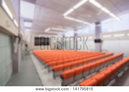 Abstract blur Rostrum with microphone and computer in conference hall. Orange color.