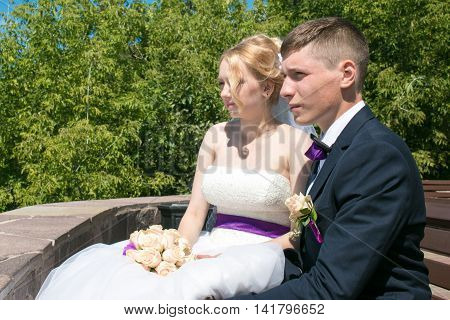 Wedding day: beautiful bride and groom sit on the bench in the park.