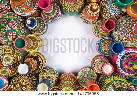 Top view showing a composition of artistic painted handcrafted pottery vases compacted around an empty circle on white background