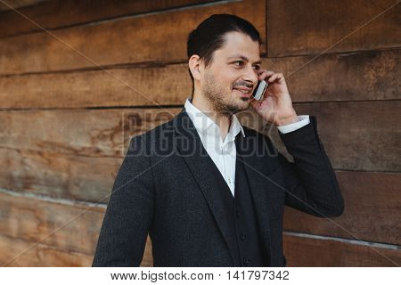 Young man chatting on a smartphone smiling with pleasure as he listens to the conversation, against a wooden background.