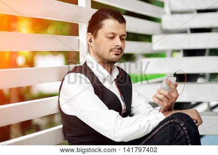 Attractive hipster man using a smartphone and listening music with earphones in the city.