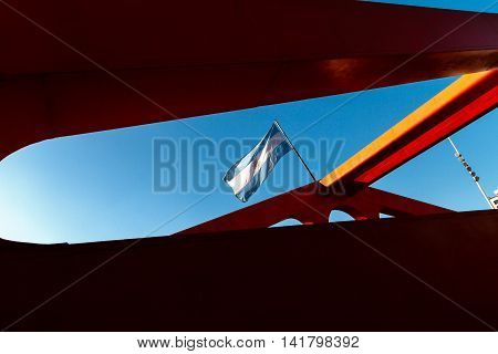 Argentina Flag Flying On The Structure Of A Bridge With Sun Backlight