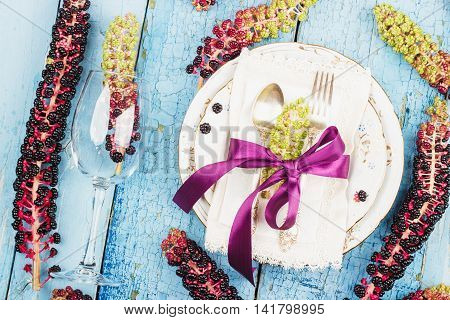 Tableware with violet flowers and silverware on the wooden background